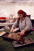 A Cree woman, Elizabeth Brien, preparing a beaver for a family feast. Northern Quebec, Canada. 1988