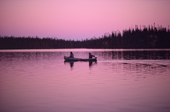 Cree trappers return from a hunting trip in their canoe at twilight. Quebec, Canada. 1988