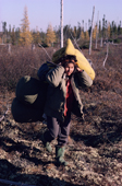 A Cree woman carries bedding and goods on a portage between waterways. Quebec. Canada. 1988