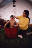 Johnnie, Cree boy is given a bath in an oil drum at a bush camp by his grandmother, Elizabeth Brien. Northern Quebec. Canada. 1988