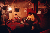 Cree family in their 'bush camp' cabin at night, lit by oil lamps. Quebec. Canada. 1988