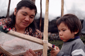 Cree woman, Elizabeth Brien, makes a snow shoe watched by her grandson. Quebec, Canada. 1988