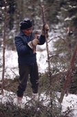 Billy Edwards, an elderly Cree trims a larch pole with his axe. Quebec. Canada. 1988