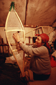 A Cree woman, Elizabeth Brien, threads caribou hide lacing onto a pair of snowshoes. Quebec, Canada. 1988
