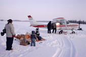 A Cree family watch supplies arrive in a small plane landed on the lake ice. Quebec. Canada. 1988