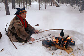 Lake Sami cooks some dried reindeer meat and coffee on his fire. Inari. Finland. 1996