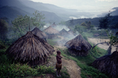 Yali girl hugs herself to keep warm in cold morning air, near her village. Irian Jaya, Indonesia. 1990