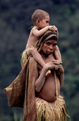 Yali woman gives a child a ride on her shoulders on the way to the fields. Irian Jaya. Indonesia. 1990