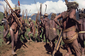Yali warriors, wearing head-dresses and carrying bows & arrows, dance at a feast. Irian Jaya, Indonesia. 1990