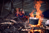 Sami herder, Johan warms himself by the fire in his tent during migration. Kautokeino, North Norway. 1985