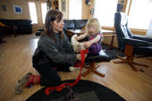 Inge Ellen, a Saami woman, helps her daughter Sara Lea put on a pair of traditional reindeer skin boots at their home near Kautokeino. Finnmark, North Norway. 2007