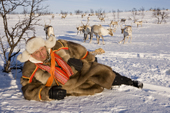 Saami reindeer herder, Nils Peder Gaup, relaxing while out keeping watch over his reindeer at their winter pastures near Kautokeino. Finnmark, North Norway. 2007