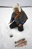 Saami reindeer herder, Nils Peder Gaup, ice fishing for Arctic Char on a lake near his reindeers' winter pastures. Kautokeino, Finnmark, North Norway. 2007