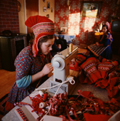Saami woman sews yards of ribbon and trim onto her wedding dress. Kautokeino. Norway. 1972
