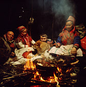 Sami family, Johan-Hendrik, Inge-Anna, Nils-Peter, Berit Logje cook over the fire in the Lavo. Migration. Norway. 1972
