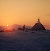Saami woman by her Lavo (tent) at sunset. Spring Migration. Finmarksviida. North Norway. 1972