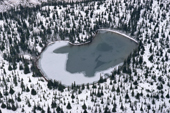 Aerial view of a lake freezing over in the autumn surrounded by snow covered boreal forest in Labrador. Canada. 1997