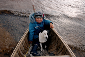 Mani, A young Innu girl, sits with a dog in a canoe during a hunting trip in Southern Labrador, Canada. 1997