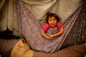 Mani, a young Innu girl, plays in a tent at her family's autumn hunting camp in Labrador, Canada. 1997