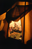 In the evening, Uniam, an Innu hunter, relaxes in his tent with his grandaughter at their autumn camp. Labrador, Canada. 1997