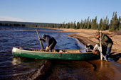Innu hunters, Uniam & Pinip, set out on a hunting trip by canoe with their dog. Southern Labrador, Canada. 1997