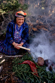 At an Innu autumn hunting camp, Enen, smokes beaver meat over an open fire. Southern Labrador, Canada. 1997