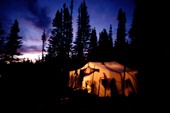At dusk, light shines from a tent at an Innu hunting camp in the forest. Southern Labrador, Canada. 1997