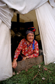 Enen, an Innu woman, sits at the entrance to a tent at an autumn  hunting camp in Southern Labrador, Canada. 1997