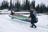 Two Innu men, portaging with their canoe during an autumn hunting trip. Labrador, Canada. 1997