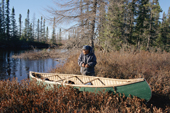 Pinip, an Innu hunter, with his canoe hauled out on the bank of a small river in the autumn. Labrador, Canada. 1997