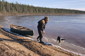 Uniam, an Innu hunter, hauls his canoe along the edge of a freezing lake in the autumn. Labrador, Canada. 1997