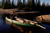 Uniam, an Innu man, using his canoe to carry firewood back to his autumn hunting camp in Southern Labrador, Canada. 1997