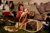 At an Innu hunting camp, Enen, threads caribou skin lacing onto a new pair of snowshoes. Labrador, Canada. 1997