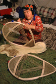 At an Innu hunting camp, Enen, threads caribou skin lacing onto a new pair of snowshoes.Southern Labrador, Canada. 1997
