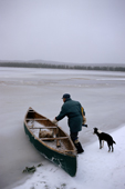 As freeze-up approaches Pinip, an Innu hunter, prepares to go out in his canoe. Labrador, Canada. 1997