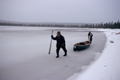 Two Innu hunters haul their canoe along the edge of a frozen lake. Labrador, Canada. 1997