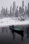 Pinip, an Innu hunter, paddles his canoe across a river in bad autumn weather. Southern Labrador, Canada. 1997