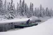 In bad weather, an Innu man travels by canoe to check his traps. Labrador, Canada. 1997