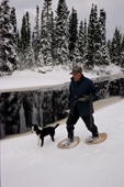 Uniam, an Innu hunter, out on snow shoes with his dog in the autumn. Southern Labrador, Canada. 1997