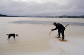 Uniam, an Innu hunter, checks the thickness of ice on a lake with his axe. Southern Labrador, Canada. 1997