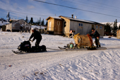 Transporting water to homes in Davis Inlet by snowmobile. Northern Labrador, Canada. 1997