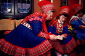 Sami women in traditional clothes share a prayer book at a christening service in Kautokeino. North Norway. 1990