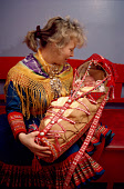 Sami mother with her baby in traditional cradle at christening. Kautokeino, Norway. 1990