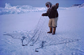 During the polar night, Inuit hunter, Ituko, dressed in furs, sets nets under the ice to catch seals. Moriussaq Northwest Greenland. 1980