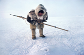 Fur clad Inuk, Qaavigannguaq, waits with his harpoon at a seal's breathing hole. NW Greenland. 1980