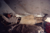 Inuit hunter in polar bear pants & seal skin Kamik rests in tent, whilst on a hunting trip. N.W.Greenland. 1980