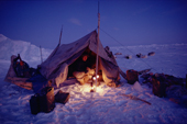 An Inuit hunter, Ituko, lights two Primus stoves to warm his tent. N.W. Greenland. 1986