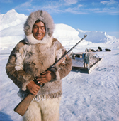 Kigutikak Duneq in fur clothing. He carries a rifle his dogs are behind him. Qaanaaq. NW Greenland. 1971