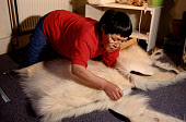 Mikivssuk Karlsen, an Inuit woman, making a pair of traditional polar bear skin trousers. N.W.Greenland. 1998