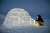 Kajutaq Avike, an Inuit hunter, about to enter an Igloo he has built at dusk. Northwest Greenland. 1998